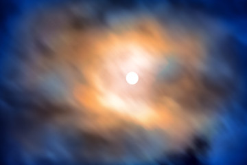 Night view at the full moon through moving blue clouds