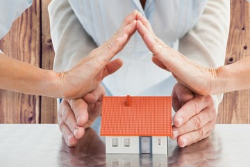 Composite image of couples hands with model house