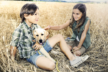 brother and sister in a wheat field with a dog