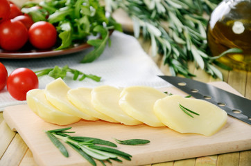 sliced cheese, tomatoes and herbs on a kitchen table closeup