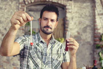 expert oenology measuring the percentage of sugar of the wine