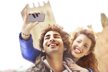 Couple in love making a selfie while him giving her a kiss