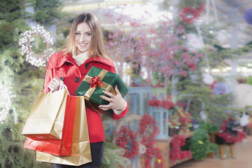 Young woman shows her gift packs inside a Christmas shop