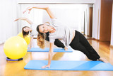 two women making a fitness exercisen in synchrony poster