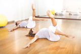 two women crossing legs in synchrony for fitness poster