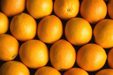 Many ripe oranges as background over black coseup