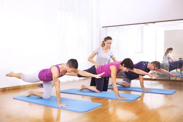 teacher explaining people fitness exercises to balance the body