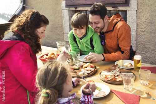 Leinwandbild Motiv Family having lunch in a chalet in mountain