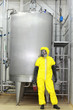 technician in  uniform  at  industrial process tank in factory