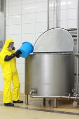 technician   with blue bucket at opened industrial process tank