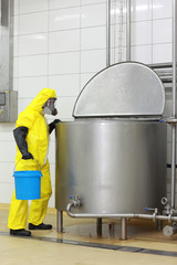technician in   coveralls  with bucket at process tank