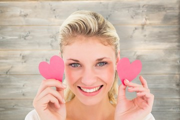 Attractive young blonde holding little hearts