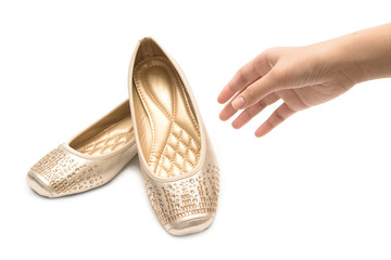 Woman hand holding pair of beige female shoes