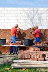 two bricklayers are building a new house