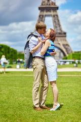 Couple kissing in Paris near the Eiffel tower