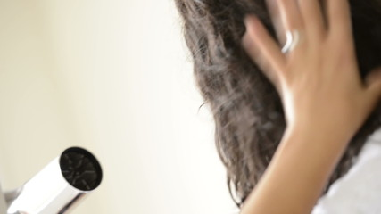 Young woman with long brown hair drying hair with blowdryer