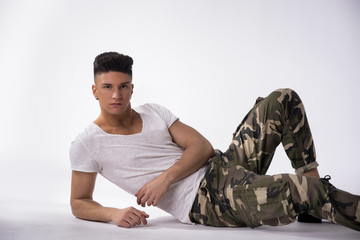 Handsome young man laying down on floor, white background