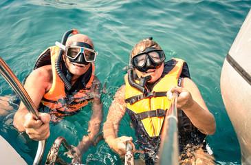 Senior happy couple using selfie stick in tropical sea excursion