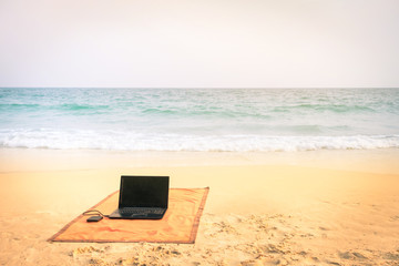 Computer laptop at the beach on vintage tropical destination