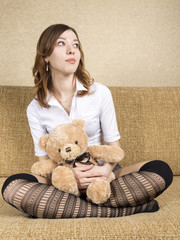 Girl sitting on the couch with the soft toy