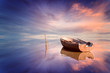 Leinwanddruck Bild - Lonely boat and amazing sunset at the sea