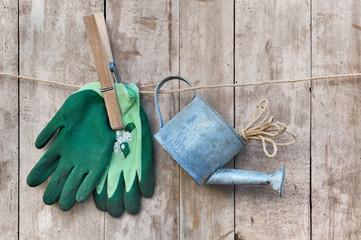 gants de jardin et arrosoir suspendus à une corde