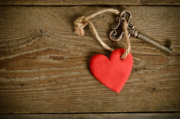 Handmade Heart with key together lying on a wooden  board