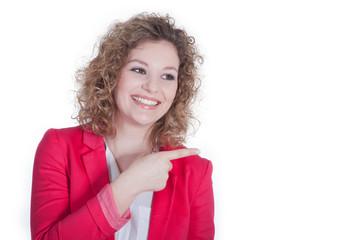 Junge Geschäftsfrau zeigt lächelnd auf leere Fläche