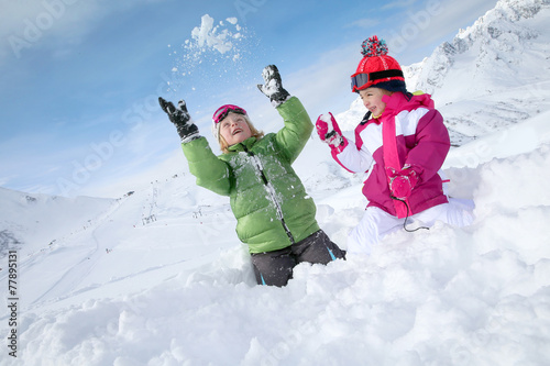 Kids having fun playing in the snow - 77895131