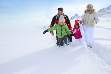 Family walking in deep snow track