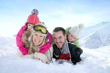 Cheerful family laid down in snow ground