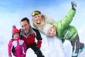 Cheerful family of 4 enjoying winter vacation