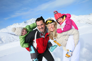 Family having fun at the top of snowy mountain