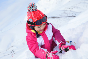 Little girl with pink outfit playing in the snow