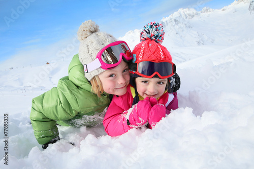 Portrait of kids enjoying winter vacation at ski resort - 77895335