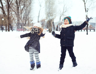 boy and girl having fun with the snow in winter park
