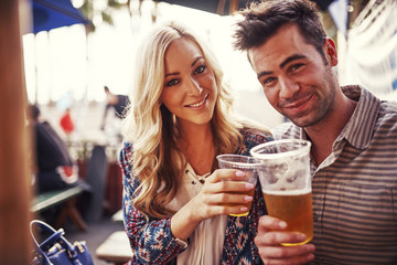 attractive couple drinking beer at outdoor restaurant