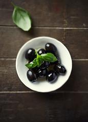 Black olives with basil leaves
