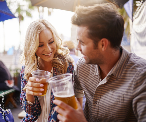 romantic couple drinking beer in plastic cups at outdoor bar - 77895941