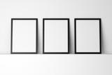 three blank black photo frames on white shelf