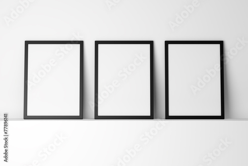 three blank black photo frames on white shelf - 77896141