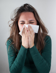 Young woman blowing her nose with paper tissue.