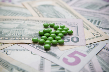 Pills on a background of money