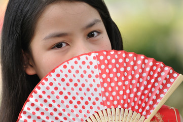 Asia female teenager wear red suit and hold a paper fan in garde