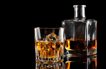 Glass of whiskey with ice and a square decanter