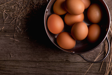 chicken eggs in pan on rustic wooden background with straw