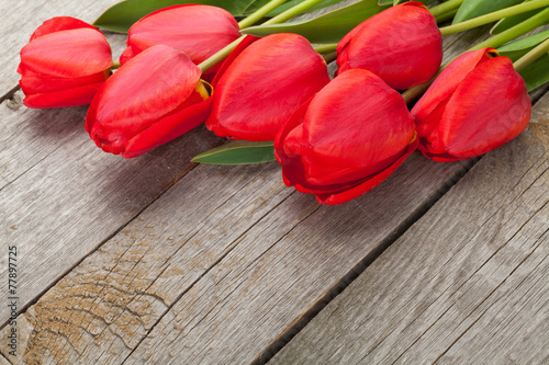 canvas print picture Fresh red tulips bouquet over wooden table background