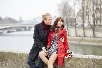 Couple at the Parisian embankment at misty day