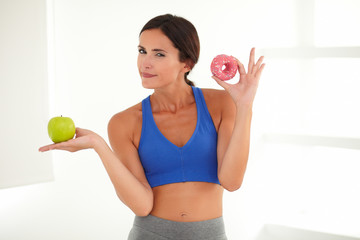 Standing pensive woman holding cake and fruit