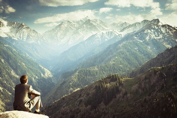 businessman at the top of the mountain sitting and thinking